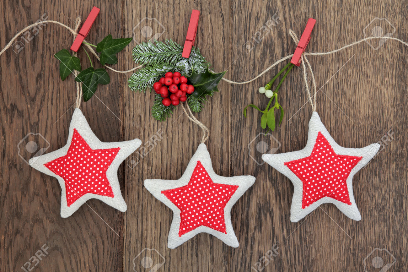 Christmas star decorations with holly, ivy, fir and mistletoe hanging on a string line over oak background.